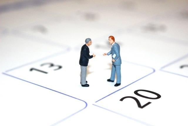 カレンダーと話し合う二人のビジネスマン