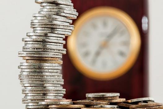 積み上がったコインと時計