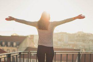 太陽に向かって伸びをする女性